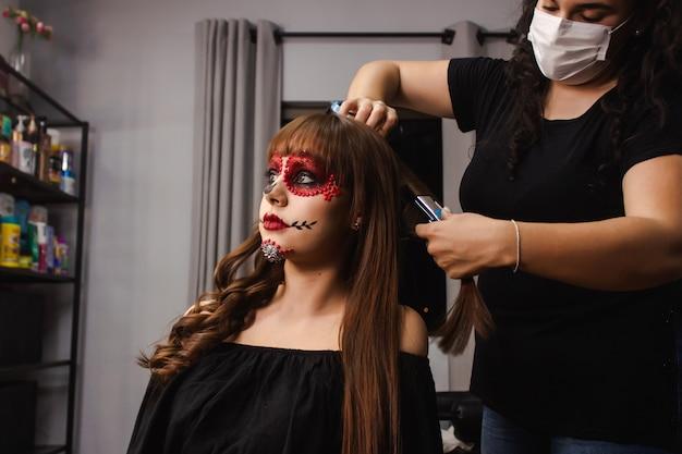 Maskenbildner kräuselt die haare eines mädchens mit dia de los muertos make-up im schönheitssalon.