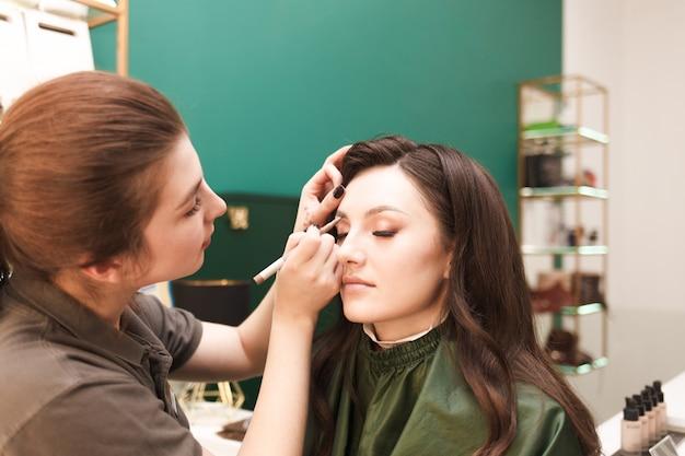 Maskenbildner macht augenbrauen make-up für seinen kunden. verfahren zum zeichnen der augenbrauen
