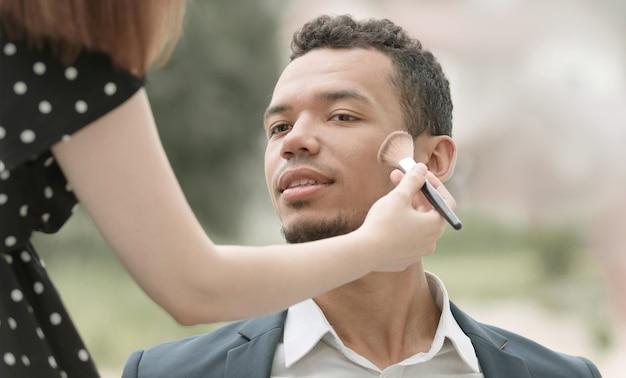 Maskenbildner macht make-up junger politiker vor einer öffentlichen rede