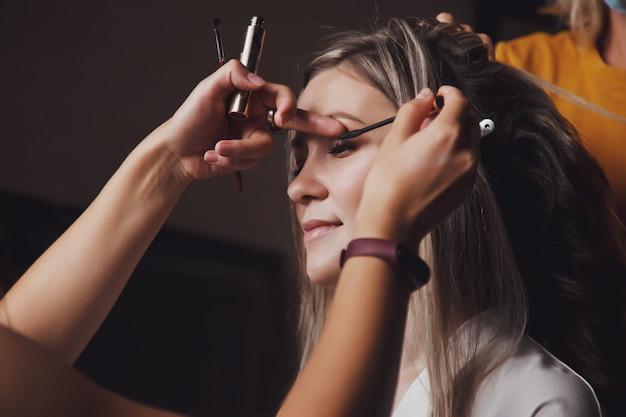 Maskenbildner machte hochzeits-make-up für süße junge braut am hochzeitstag im hotelzimmer. hübsche junge frau macht sich bereit, den bräutigam zu treffen. konzept von glück und luxus verheiratet. platz kopieren