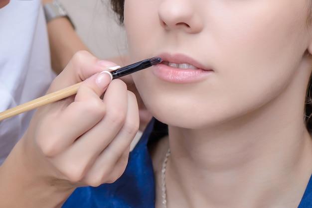 Maskenbildner malt die lippen des mädchens mit einem pinsel