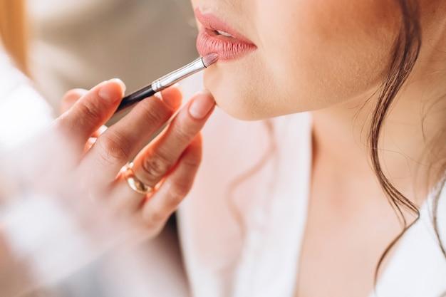 Maskenbildner malt lippen einer schönen braut. zarter morgen der braut. junges mädchen malt lippen mit einem pinsel in einem sanften schatten.