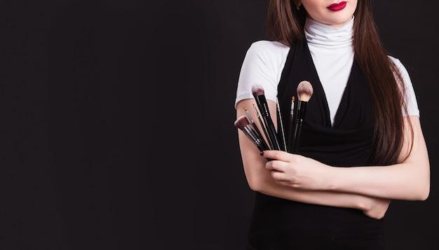 Maskenbildner mit pinseln in der hand auf einer schwarzen wand