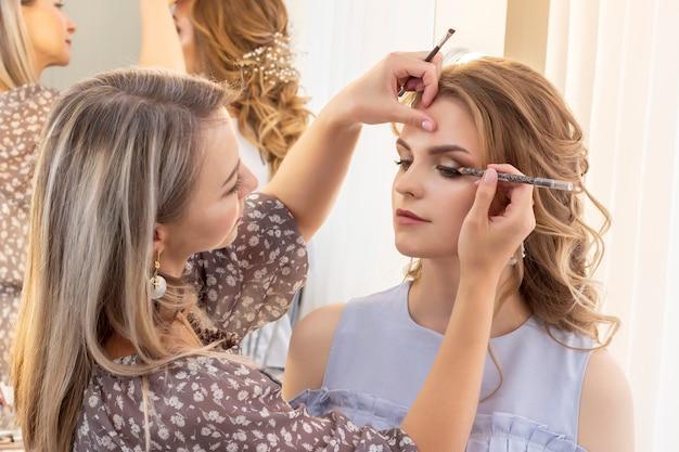 Maskenbildner schminken mädchenmodell. hochzeits make-up, abend make-up, natürliches make-up. visagistin legt lidschatten auf die augenlider.