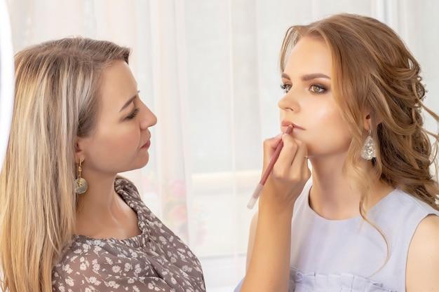 Maskenbildner schminken mädchenmodell. hochzeits make-up, abend make-up, natürliches make-up. visagistin malt lippen von mädchen