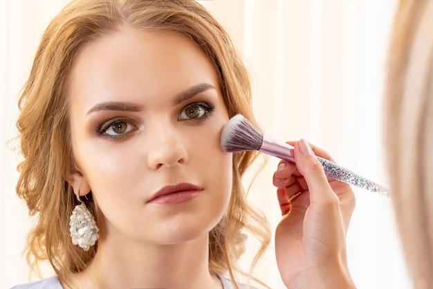 Maskenbildner schminkt das mädchenmodell. pinsel gilt schatten, concealer. schönes mädchenmodell, porträt. nude-farben im make-up. hochzeits-make-up, abend-make-up.
