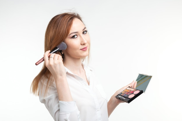 Maskenbildner-, schönheits- und kosmetikkonzept - koreanische visagistin mit make-up-pinseln und lidschatten-palette