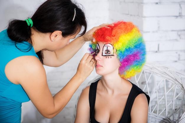 Maskenbildner setzt mädchenclownmake-up in studio ein