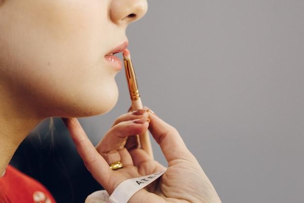 Maskenbildner trägt den lippenstift mit dem pinsel auf die lippen einer jungen frau auf