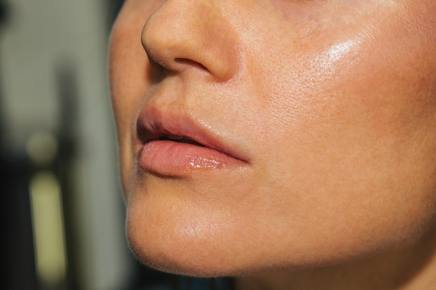 Maskenbildner trägt rosa lippenstiftglanz auf. schönes weibliches gesicht. hand von lippen eines make-upmeister-malens eines schönheitsmodells des jungen mädchens. make-up läuft.