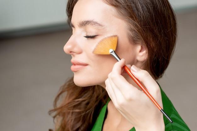 Maskenbildner trockene kosmetische tongrundierung auf dem gesicht mit make-up-pinsel, schönheit mit perfektem natürlichem make-up, das rouge aufträgt.