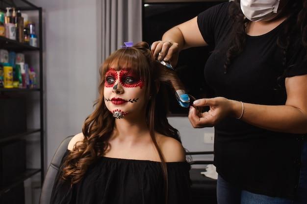 Maskenbildnerin kräuselt die haare eines mädchens mit dia de los muertos make-up.