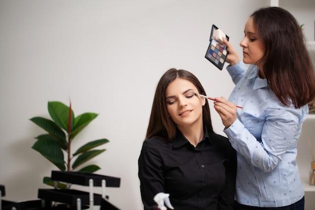 Maskenbildnerin macht professionelles make-up für die klientin bei ihr zu hause