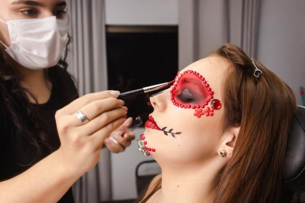 Maskenbildnerin malt die ränder der augen eines mädchens mit dia de los muertos make-up.