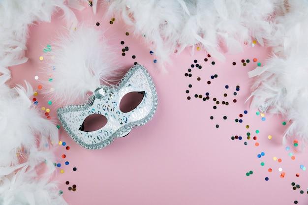 Maskeradekarnevalsfedermaske mit bunten konfettis und boafeder auf rosa hintergrund
