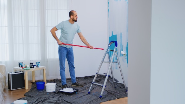 Maskieren von blauer farbe mit einem in weiße farbe getauchten walzenpinsel. handwerker renovieren. wohnungsrenovierung und hausbau während der renovierung und verbesserung. reparieren und dekorieren.
