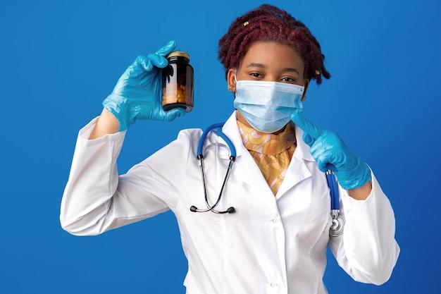 Maskierte afroamerikanische ärztin, die glas medizin vor blauem hintergrund zeigt showing