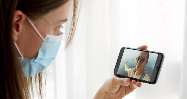 Maskierte frau, die auf videoanruf mit ihrer freundin spricht