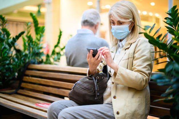 Maskierte frau, die ihr handy benutzt, während sie in einem einkaufszentrum sitzt