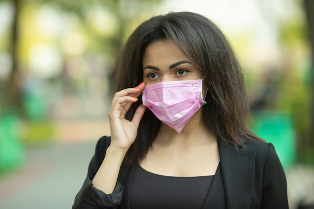 Maskierte frau - schutz gegen influenzaviren. afroamerikanische frau, die maske zum schutz trägt.