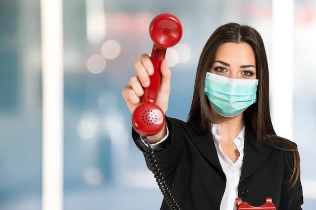 Maskierte geschäftsfrau, die ein altes telefon während der coronavirus-pandemie verwendet