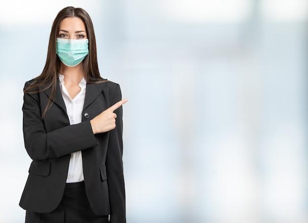 Maskierte geschäftsfrau, die ihren finger auf einen hellen raum zeigt