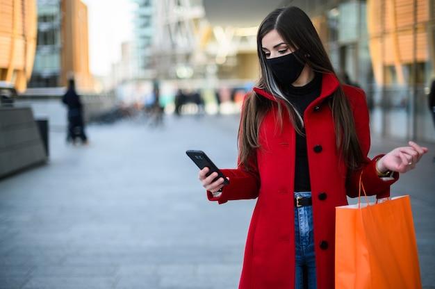 Maskierte junge frau, die in einer stadt geht, während sie ihr handy benutzt