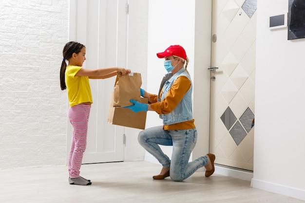 Maskierte lieferfrau liefert lebensmittel während des virusausbruchs, der coronavirus-panik und der pandemien.