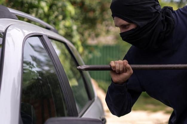 Maskierter dieb, der in der nähe des autos steht und versucht, das fenster mit einer cowbar einzuschlagen