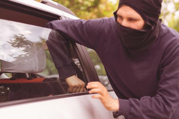 Maskierter dieb entriegeln und öffnen sie das autofenster, um eigentum zu stehlen