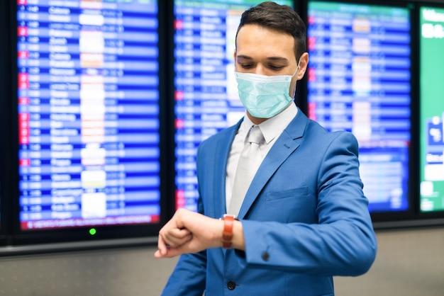 Maskierter geschäftsmann, der zeit im flughafen prüft, flugverspätung während des coronavirus-pandemiekonzepts