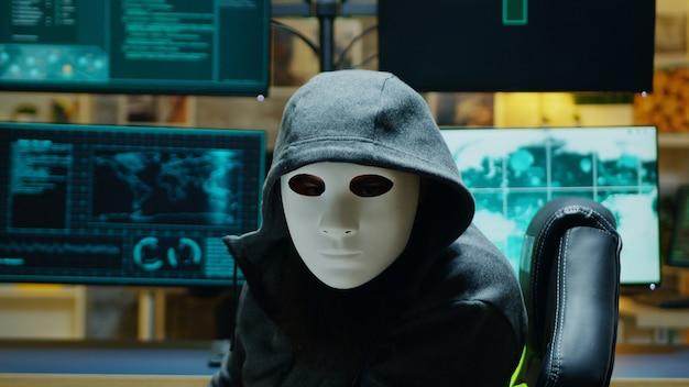 Maskierter hacker in seiner wohnung, der in die kamera schaut, während er online-informationen stiehlt.