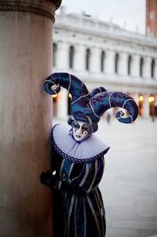 Maskierter mann mit harlekincharakter bei der venezianischen maskerade späht hinter einer säule in der straße von venedig hervor