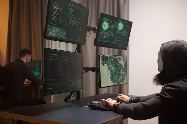 Maskierter und gefährlicher hacker vor computer. verwundbare regierung