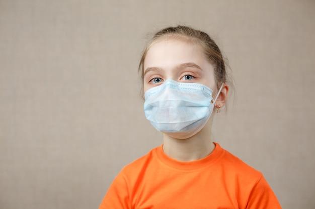 Maskiertes kind - schutz vor viren. kleines kaukasisches mädchen, das maske für covid 19 trägt. biologische waffen. epidemie pandemie.