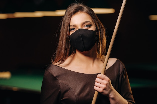 Maskiertes mädchen in einem poolclub mit einem queue in der hand