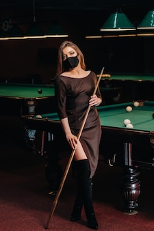 Maskiertes mädchen in einem poolclub mit einem stichwort in den händen