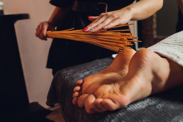 Massage der weiblichen füße mit bambusstöcken