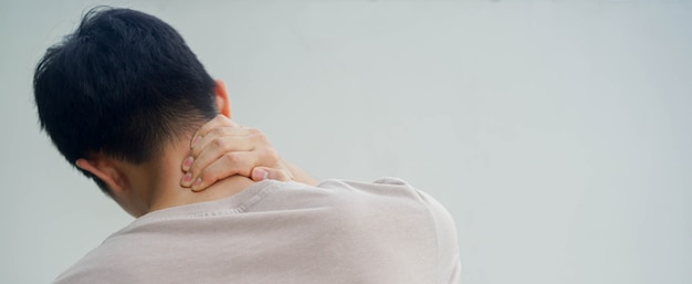 Massage des jungen mannes am nacken, um das symptom von nackenschmerzen zu lindern