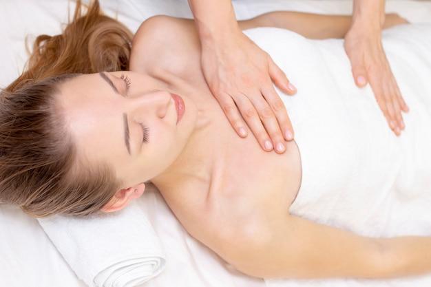 Massage und körperpflege. badekurortkörpermassagefrau übergibt behandlung. frau, die massage im badekurortsalon für schönes mädchen hat