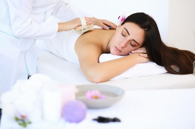 Massage und körperpflege. spa körpermassage behandlung. frau, die massage im spa-salon hat.
