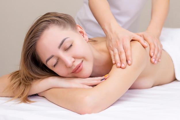 Massage und körperpflege. spa körpermassage frau hände behandlung. frau, die massage im spa-salon für schönes mädchen hat