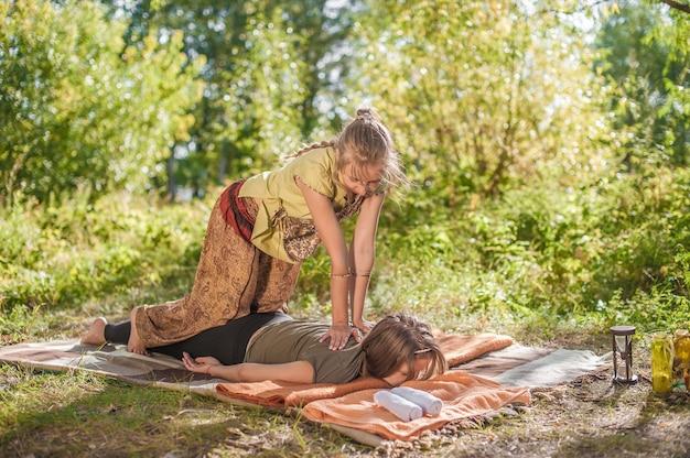 Massagemädchen gibt ihrem kunden draußen eine erfrischende massage.