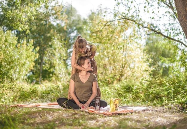 Massageprofi führt angemessen eine großartige massage auf dem waldboden durch.