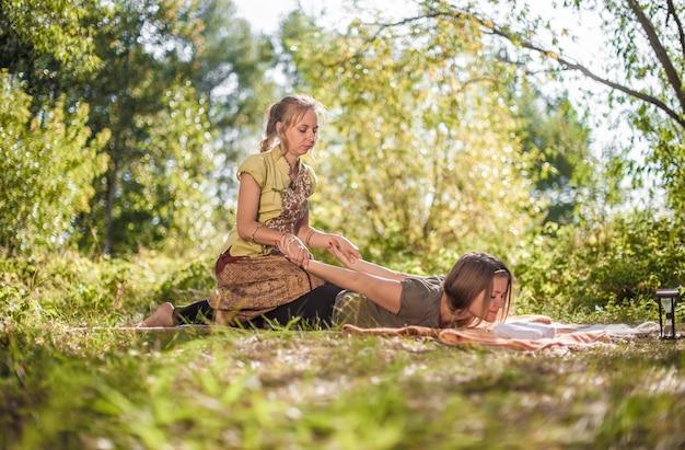 Massageprofi führt eine entspannende massage auf dem waldboden durch