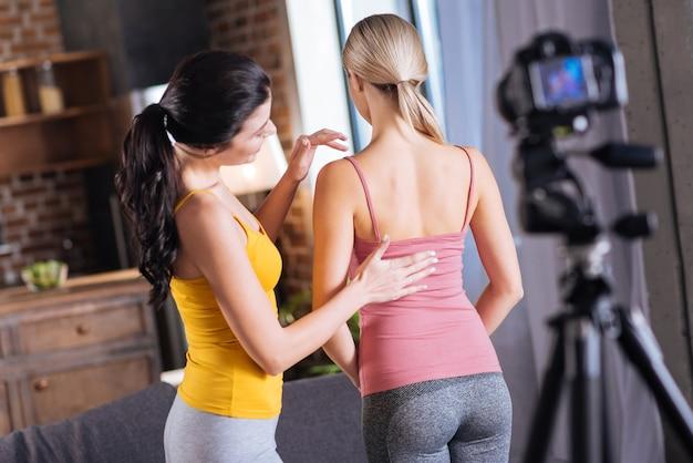 Massagetechnik. positive nette junge frau, die vor ihrer freundin steht und auf ihren rücken schaut, während sie massagetechniken präsentiert