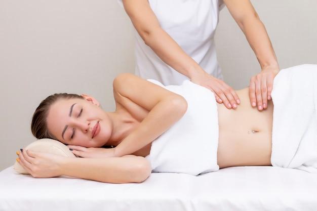 Massagetherapeut, der den magen einer frau massiert. massage und körperpflege. badekurortkörpermassagefrau übergibt behandlung.