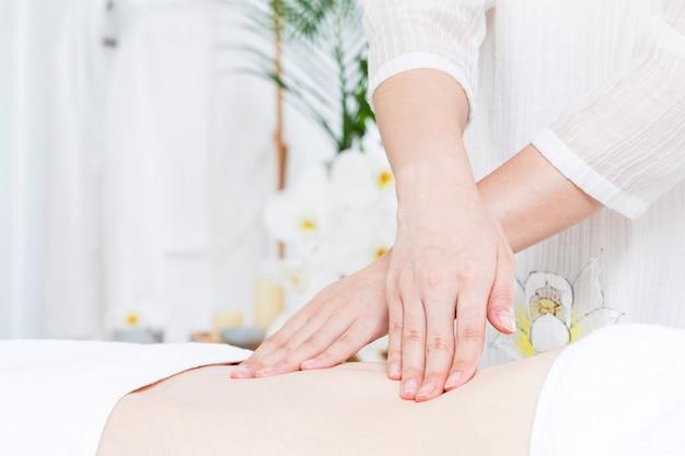 Massagetherapeutin massiert den bauch einer frau