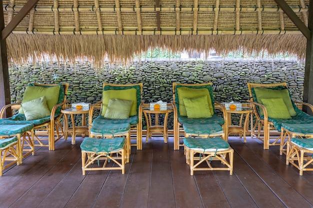 Massagetisch mit blick auf den tropischen garten. spa-massageraum mit fußmassagesesseln auf der tropischen insel bali, indonesien
