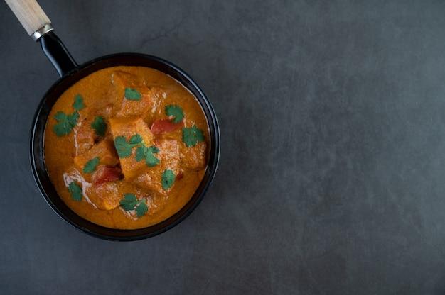 Massaman curry in einer pfanne auf dem zementhintergrund